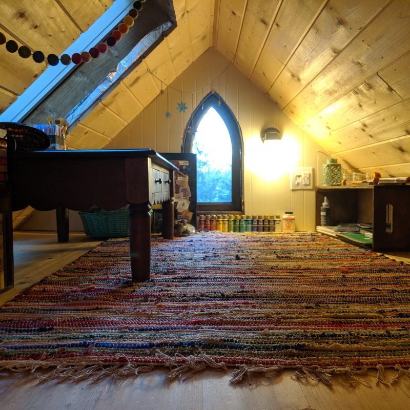 Amanda's tiny house art studio loft complete with rainbow rug and coffee table being used as a desk.